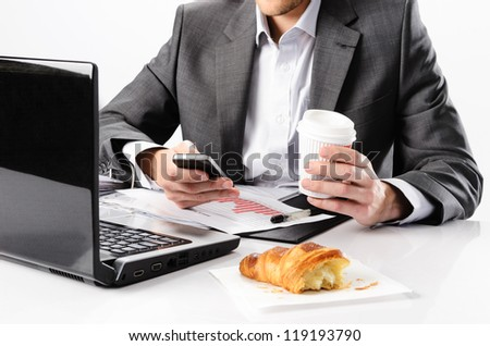 Anonymous business man types on smartphone while having a coffee and snack at his desk with laptop computer and documents