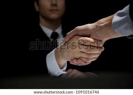 Anonymous business partners making handshake in dark shadow Stockfoto ©