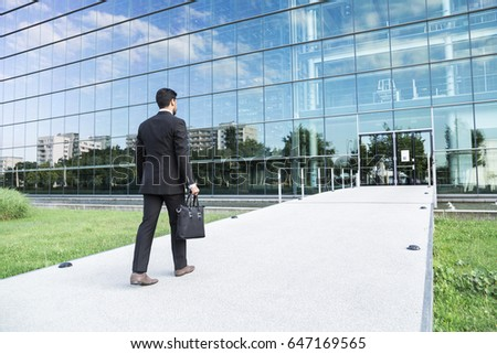 Anonymous businessman or worker in black suit with leather handbag or laptop case in his hand goes to work on the road to the entrance of a glass office building. #647169565