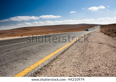 Anonymous car driving toward the viewer on a desert road.