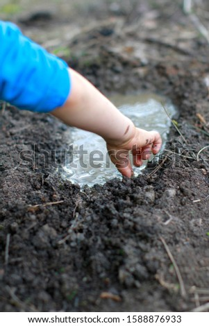 Anonymous child arms and hands playing with mud and water, testing ground textures, learning about nature, environment and Earth, real life
