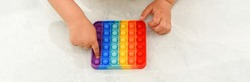 Anonymous child with colorful poppit game. Close up bunner shot of kid hands playing with colorful pop It fidget toy.