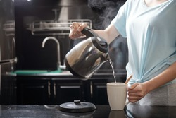 Anonymous female filling mug with hot water while brewing beverage in kitchen