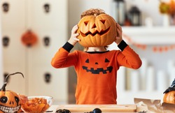 anonymous funny ginger boy in a costume with a pumpkin  Jack o lantern for a head during a Halloween celebration