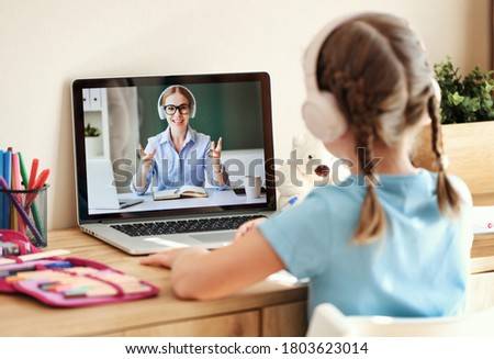 Anonymous girl in headphones sitting at table and listening to friendly teacher smiles and tells interesting stories during online lesson at home