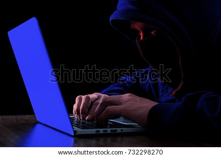 Anonymous hacker with laptop in the dark. Cyber security concept #732298270