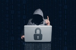 Anonymous hacking and using computer to pirate passwords with the padlock symbol on the laptop. Dark background and binary 0 and 1