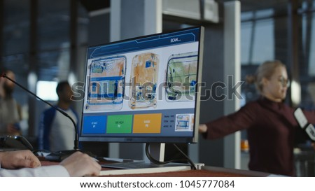 Anonymous man at checkpoint in airport exploring luggage on screen with x-ray.