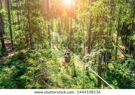 Anonymous man flying above a pine tree forest on a roulette wheel pulley. Adventure park close-up. High rope courses activity. Summer fun and sports for adventurous people. CHallenge yourself