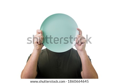Anonymous man hiding his identity, covering face using an empty dish plate. Global crisis and hunger issue. Food supply problem. Conceptual message, starvation and famine after drought season. Stock photo ©