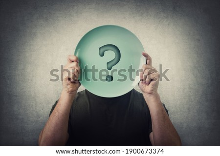 Anonymous man hiding his identity, covering face using an empty dish plate with question mark. Global crisis, food supply problem. Conceptual message, starvation and famine issue. Hunger diet concept Stock photo ©