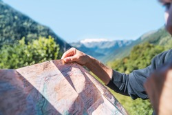 Anonymous man looking the travel route on a map in the mountain. Routes, excursions and mountain trails through nature in summer. Concept of exploring and live adventures traveling in nature.