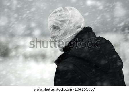 Anonymous person with bandaged head under the nuclear snowstorm