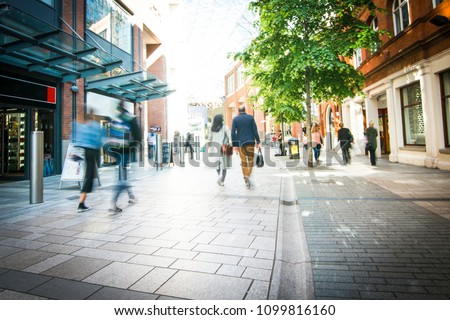 Anonymous shoppers walking on a shopping high street