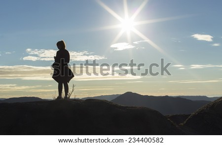Anonymous silhouette female runner standing on a mountain top and checking her playlist on her music device as the sun flares in the background