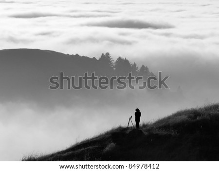 Anonymous silhouette of photographer overlooking a blanket of fog over Pacific Ocean and the Santa Cruz Mountains in California
