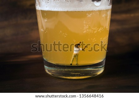 Anonymous, unrecognizable miniature man in a glass of beer. Binge drinking concept. Tiny person with a drinking problem at a crazy party. Last call, or time to seek help with a drinking problem.