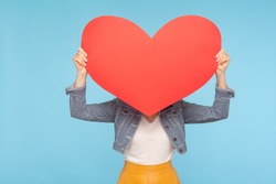 Anonymous woman in casual outfit hiding face behind huge red heart, concept of secret love fondness, unknown lover and affair, romance on Valentines day. indoor studio shot isolated on blue background