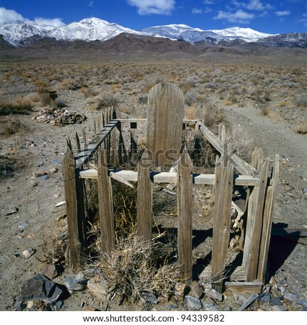 Anonymous wooden grave in the desert.At the background mountains with snow