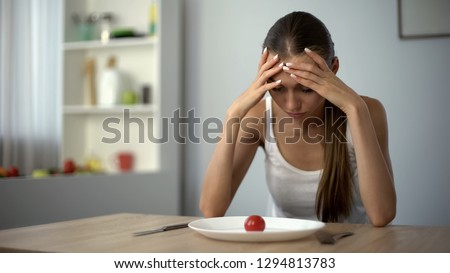 Anorexic girl feels dizzy, depleted by severe diets, exhausted body, starvation Stock photo ©