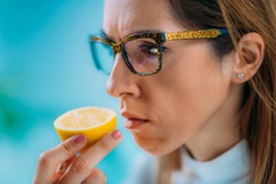 Anosmia or smell blindness, loss of the ability to smell, one of the possible symptoms of covid-19, infectious disease caused by corona virus. Woman Trying to Sense Smell of a Lemon