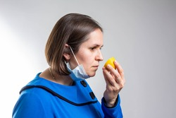 Anosmia or smell blindness, loss of the ability to smell, one of the possible symptoms of covid-19, infectious disease caused by corona virus. Man Trying to Sense Smell of a Lemon, side view.