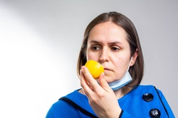 Anosmia or smell blindness, loss of the ability to smell, one of the possible symptoms of covid-19, infectious disease caused by corona virus. Man Trying to Sense Smell of a Lemon