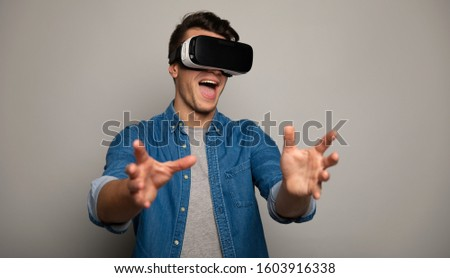 Another dimension. Close up photo of a stunned man in denim outfit, who is wearing VR glasses and stretching his hands towards the camera.