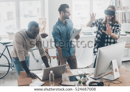 Photo of Another reality is here! Group of young business people working and communicating together while one of them wearing VR headset in creative office
