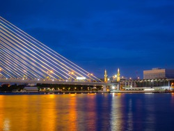 Another view of Rama VIII bridge with its reflection in Chao Phraya River, Bangkok, Thailand at the blue hour. Beautiful bridge across the Chao Phraya river: photo from Rama VIII park.