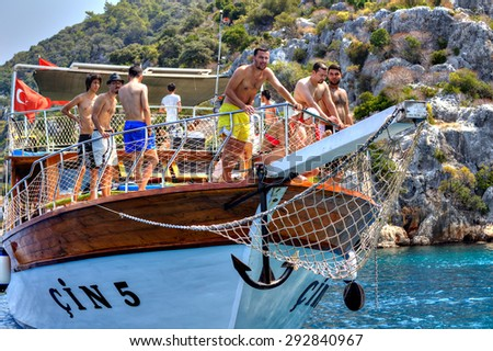 Antalya, Turkey - August 28, 2014: Water tourism, excursion walk on a yacht in the Mediterranean Sea, Turkish men and a woman relaxing on the deck of a tourist boat on a sunny summer day.