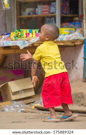 ANTANANARIVO, MADAGASCAR - JUNE 30, 2011: Unidentified Madagascar boy runs at the market. People in Madagascar suffer of poverty due to the slow development of the country