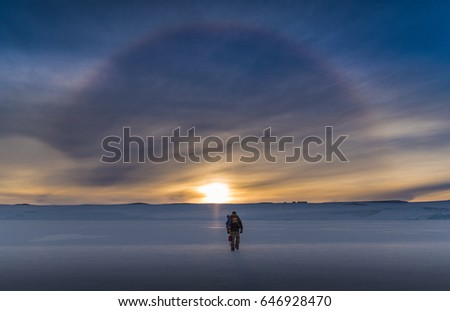 Antarctic Explorer walking towards solar halo #646928470