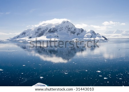 antarctic mountain with glacier is reflected in paradise harbour