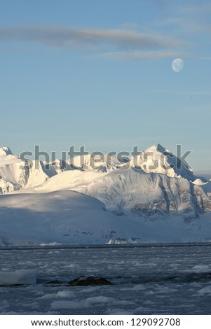 Antarctic mountains under the moonlight on a summer day.