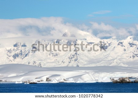 Antarctic ocean, Antarctica. Glacier Snow Covered Mountain. Dramatic blue Sky background #1020778342