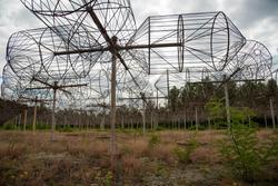 Antenna Array. A long row of radio telescopic antennas against a background of blue sky and green grass. Array of radio-telescopes