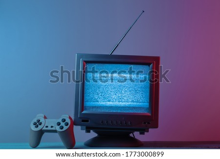 Antenna old-fashioned  tv receiver with gamepad in pink blue gradient neon light. Retro media, entertainment 80s, retro wave