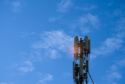 Antenna transmitting for mobile phones and smartphones with 4G and 5G internet systems. High-speed signal transmission network that supports 6G systems in the future. Copy space, blue sky with clouds