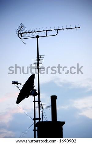 antennas and satellite dish in silhouette over a blue sunset sky
