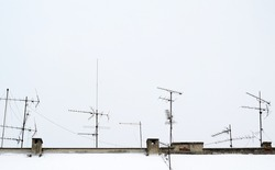 antennas on roof covered with snow