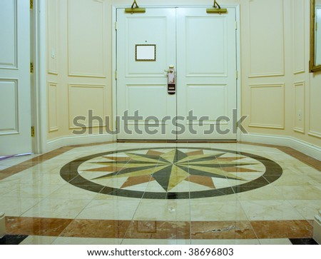 Anteroom with white double door and mosaic marble floor