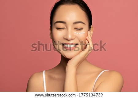 Anti aging eye cream. Young Beautiful model posing aginst pink background with applyed cream under her eyes