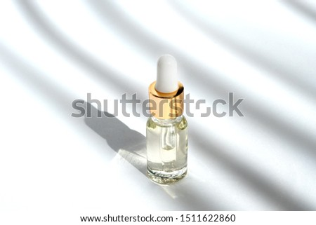 Anti aging serum with collagen and peptides in glass bottle with dropper on white background with shadows. Anti-age product, luxury body care and organic science concept.