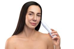 Anti aging treatment. Middle aged woman using plasma pen for a non-invasive skin rejuvenation.