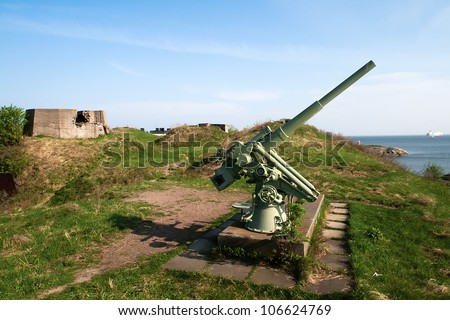 Anti-aircraft gun in the background of blue sea in Scandinavia