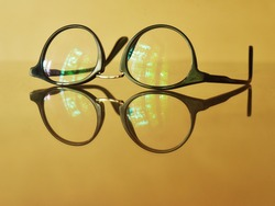 Anti-glare coating on eye glasses filters out short wavelength colors in the visible spectrum. Eye glasses on yellowish brown background.