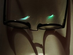 Anti-glare or anti-reflective coating on a pair of eye glasses reflects blue light from sunlight. Concept of protection of eyes from radiation from computer screen.