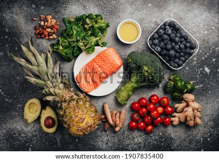 Anti inflammatory diet concept. Set of foods that help to reduce inflammation - plant based ingredients, fresh fruit, green vegetables. Healthy diet products, top view, stone background. Toned