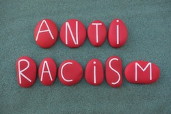 Anti Racism, social issue slogan text composed with red colored stone letters over green sand